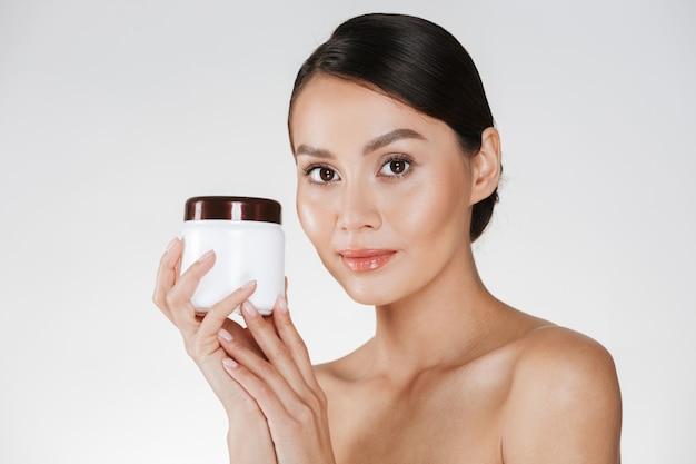 Retrato da beleza da jovem mulher bonita com pele macia e saudável, segurando o creme para o rosto com umidade e olhando para a câmera, isolada sobre o branco