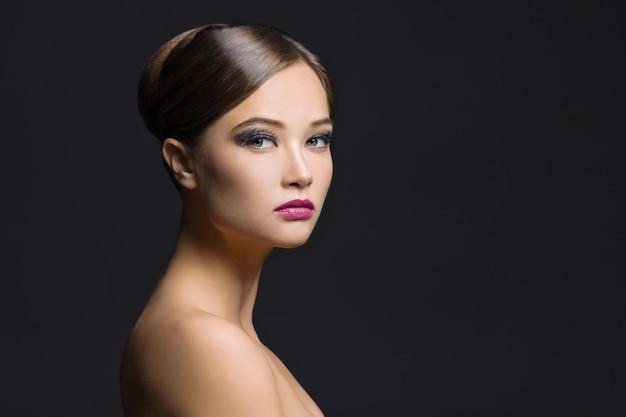 Retrato da beleza da jovem mulher no escuro