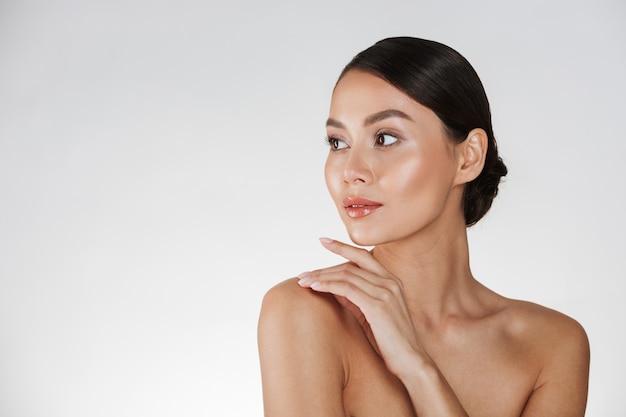 Retrato da beleza da jovem mulher olhando para longe e tocando seu ombro nu, isolado sobre o branco