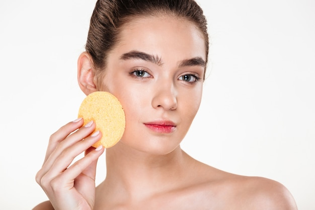 Retrato da beleza da jovem mulher seminua usando esponja de maquiagem no rosto e olhando