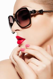 Retrato da beleza da modelo usando óculos escuros, batom vermelho e manicure rosa