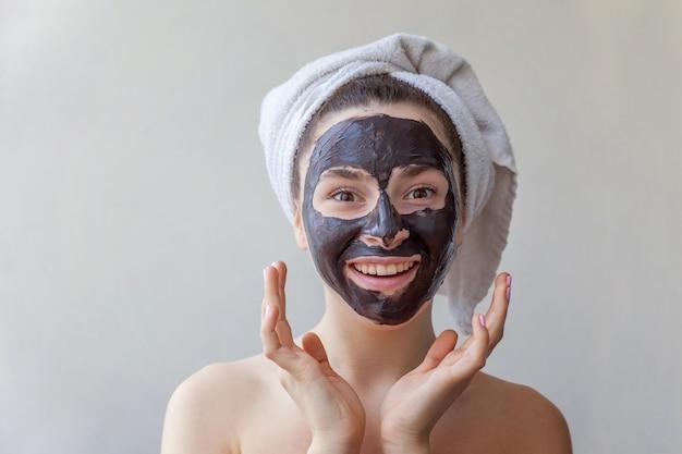 Retrato da beleza da mulher aplicar máscara nutritiva preta no rosto