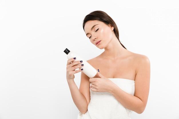 Retrato da beleza da mulher asiática em toalha segurando a garrafa com creme hidratante ou óleo nas mãos, isolado sobre o branco