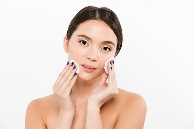 Retrato da beleza da mulher asiática morena com pele macia e saudável, removendo a maquiagem com duas almofadas de algodão, isoladas sobre o branco