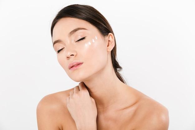 Retrato da beleza da mulher asiática, posando com creme no rosto, isolado sobre o branco