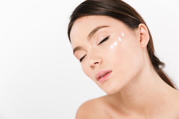 Retrato da beleza da mulher asiática, posando com creme no rosto, isolado sobre whitecloseup