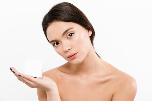 Retrato da beleza da mulher asiática seminua segurando o creme para o rosto na palma da mão, isolado sobre o branco