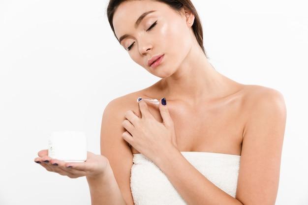 Retrato da beleza da mulher asiática sensual com os olhos fechados e setas pretas, segurando o creme para o rosto na palma da mão, isolado sobre o branco