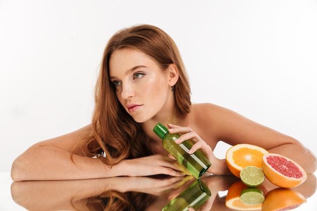 Retrato da beleza da mulher bonita ruiva com cabelos longos, reclina na mesa de espelho perto das frutas e frasco de loção