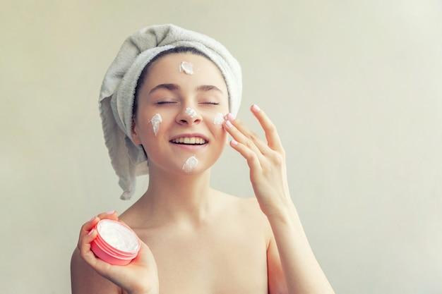 Retrato da beleza da mulher em toalha na cabeça com máscara nutritiva branca ou creme no rosto