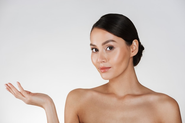 Retrato da beleza da mulher encantadora, com cabelos castanhos no coque, olhando para a câmera e demonstrando algo na palma da mão, isolado sobre o branco