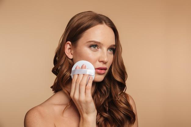 Retrato da beleza da mulher misteriosa ruiva com cabelos longos, olhando para longe enquanto remove maquiagem na bochecha