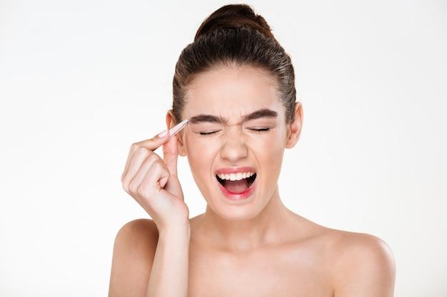 Retrato da beleza da mulher morena sensual com cabelo no coque, gritando de dor enquanto arranca as sobrancelhas com uma pinça