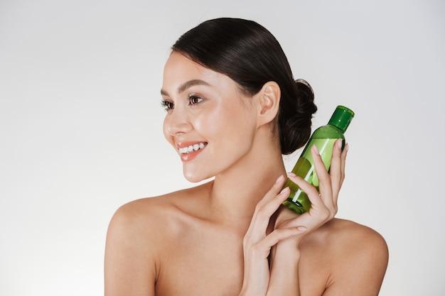 Retrato da beleza da mulher morena sorridente com pele macia e saudável, segurando a loção para remover a maquiagem, isolada sobre o branco