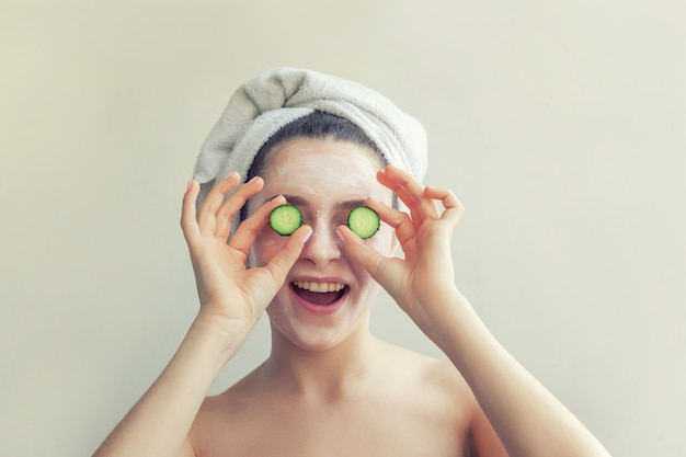 Retrato da beleza da mulher na toalha na cabeça com máscara nutritiva branca ou creme no rosto segurando fatias de pepino