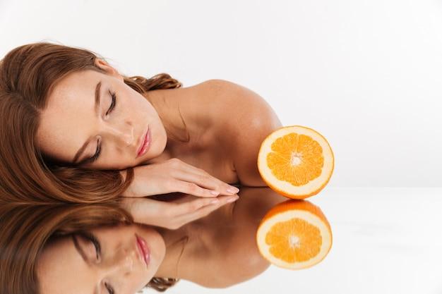 Retrato da beleza da mulher ruiva, cabelos longos, deitado na mesa de espelho perto da laranja fresca