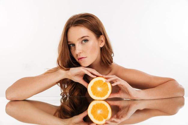 Retrato da beleza da mulher ruiva com cabelo comprido reclina na mesa de espelho enquanto posava com laranja e olhando