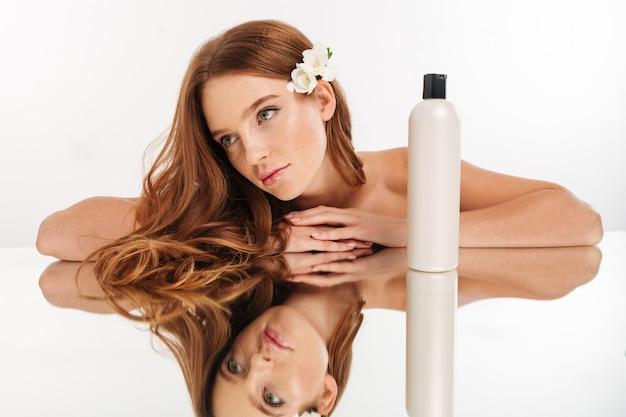 Retrato da beleza da mulher ruiva com flor no cabelo reclina na mesa de espelho com uma garrafa de loção