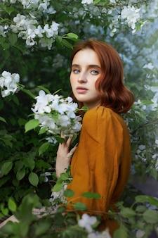Retrato da beleza da mulher ruiva na primavera nos galhos de uma macieira