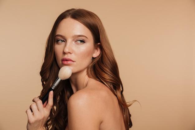 Retrato da beleza da mulher ruiva sensual com cabelos longos, posando para o lado enquanto olhando para longe e segurando a escova de cosméticos