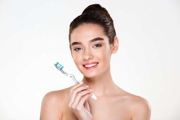 Retrato da beleza da mulher seminua bonita saudável, escovar os dentes com escova de dentes com higiene bucal