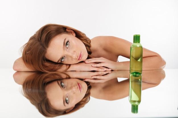 Retrato da beleza da mulher sensual gengibre com cabelos longos, deitado na mesa de espelho com uma garrafa de loção enquanto olha