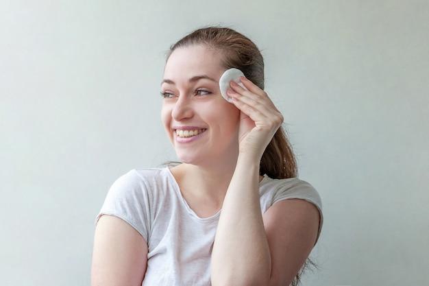Retrato da beleza da mulher sorridente com pele macia e saudável, removendo a maquiagem com almofada de algodão, isolada no fundo branco.
