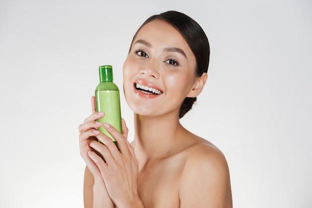 Retrato da beleza da mulher sorridente com pele saudável macia, sorrindo e segurando o removedor de maquiagem, isolado sobre o branco