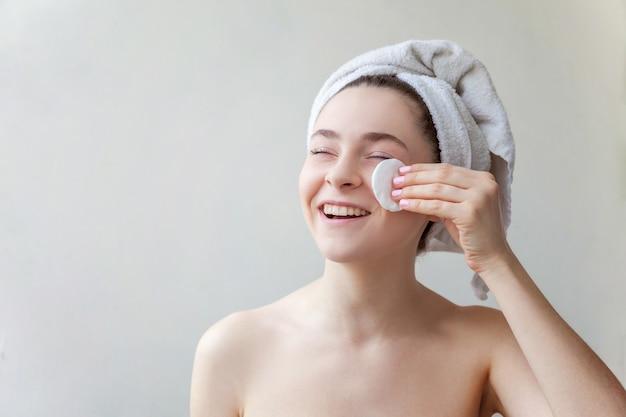 Retrato da beleza da mulher sorridente em uma toalha na cabeça com pele macia e saudável, removendo a maquiagem com almofada de algodão, isolada no fundo branco. conceito de relaxamento e limpeza de skincare