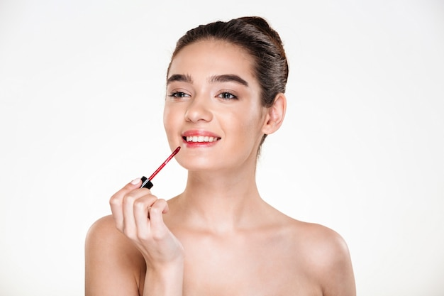 Retrato da beleza da senhora seminua bonita com cabelo em coque aplicando gloss vermelho com sorriso e olhando de lado