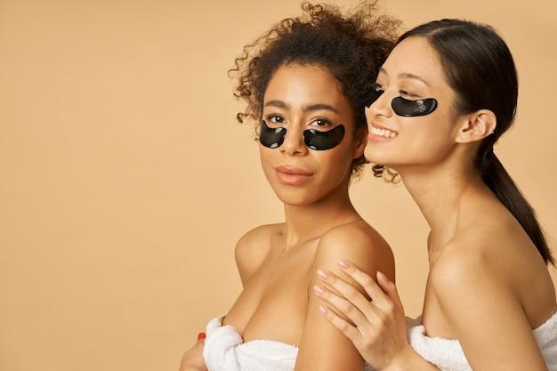 Retrato da beleza de duas jovens alegres posando com hidrogel preto aplicado sob o tapa-olho