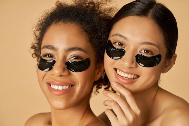 Retrato da beleza de duas jovens animadas posando com tapa-olho preto aplicado