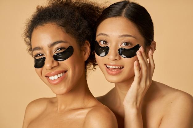 Retrato da beleza de duas mulheres felizes posando com tapa-olho preto aplicado