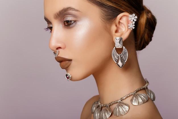 Retrato da beleza de jovem com linda maquiagem, parece no perfil, brincos e joias de colar, cabelo arranjado.