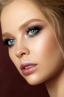 Retrato da beleza de jovem com maquiagem moda. pele perfeita e maquiagem colorida nos olhos esfumados. sensualidade, paixão, conceito moderno de maquiagem luxuosa.