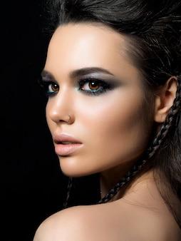 Retrato da beleza de jovem com pele perfeita e maquiagem de noite posando sobre fundo preto