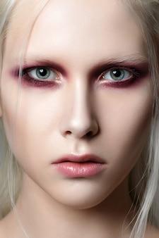Retrato da beleza de jovem com sobrancelhas brancas e cabelo. pele perfeita e maquiagem fashion. olhos vermelhos esfumados. sensualidade, paixão, conceito de maquiagem jovem da moda.