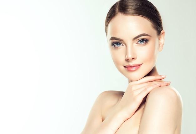 Retrato da beleza de jovem vestida de maquiagem delicada com batom rosa.