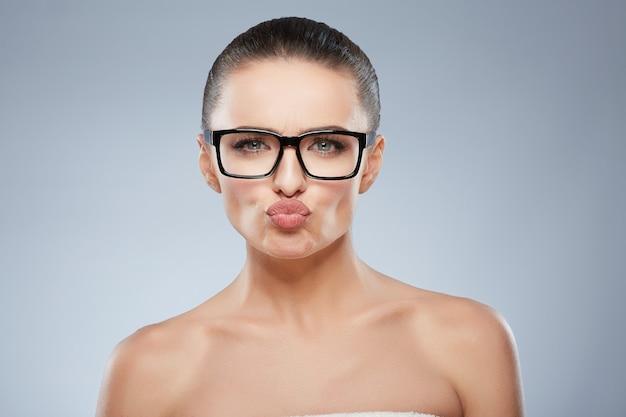 Retrato da beleza de menina de óculos, olhando para a câmera e beijando o ar. cabeça e ombros de uma mulher bonita com lábios franzidos, beicinho, lábios em arco de cupido. maquiagem natural, estúdio