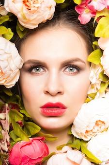 Retrato da beleza de mola de uma mulher bonita de pele clara com peônias em torno de um close-up. fundo de flores.