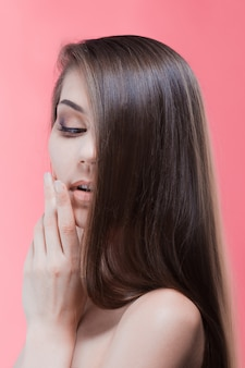 Retrato da beleza de morena com cabelo perfeito, em uma parede rosa. cuidado capilar