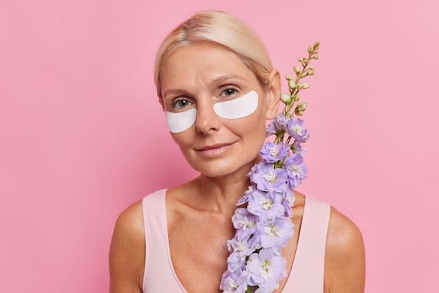 Retrato da beleza de mulher de meia-idade de cabelos louros aplica manchas de beleza sob os olhos, segura flor, usa produtos naturais para cuidados com a pele, olha diretamente para a frente, isolado sobre a parede rosa do estúdio.