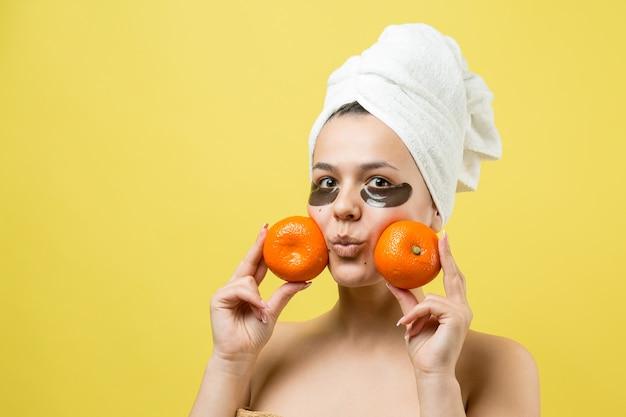 Retrato da beleza de mulher em uma toalha branca na cabeça com uma máscara nutritiva de ouro no rosto. skincare cleansing eco orgânico cosmético spa relaxa conceito. uma garota está de costas segurando uma tangerina laranja.