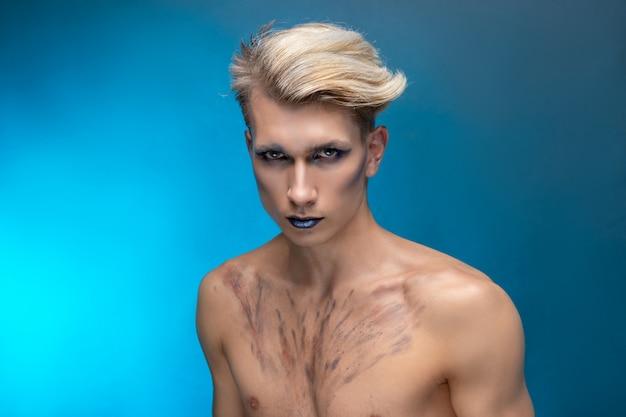 Retrato da beleza de um jovem atraente com maquiagem profissional e cabelo loiro voador