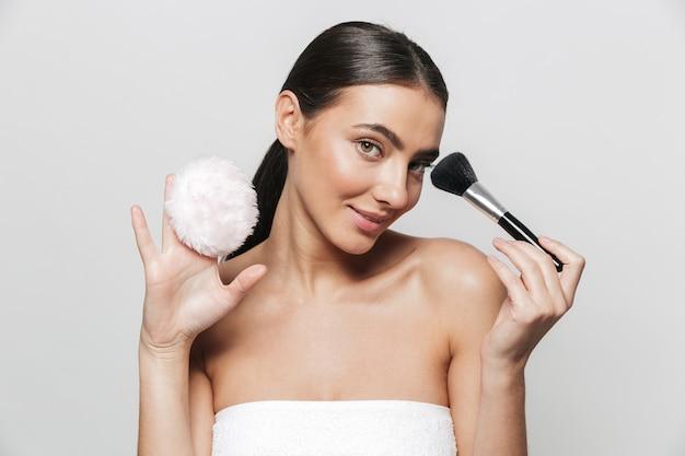 Retrato da beleza de uma bela jovem enrolada em uma toalha de pé isolado, segurando um pincel de pó de arroz e um pincel de maquiagem