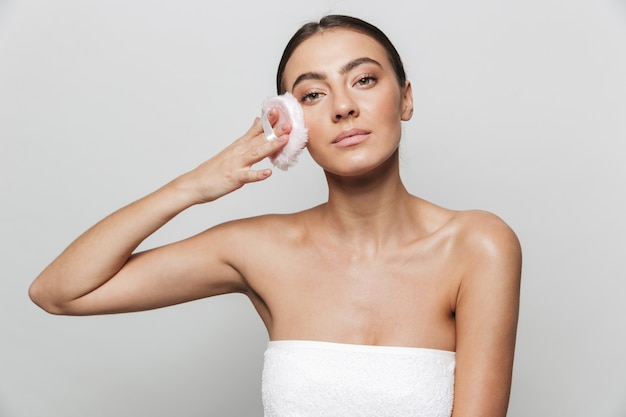 Retrato da beleza de uma bela jovem enrolada em uma toalha isolada, segurando uma esponja de pó
