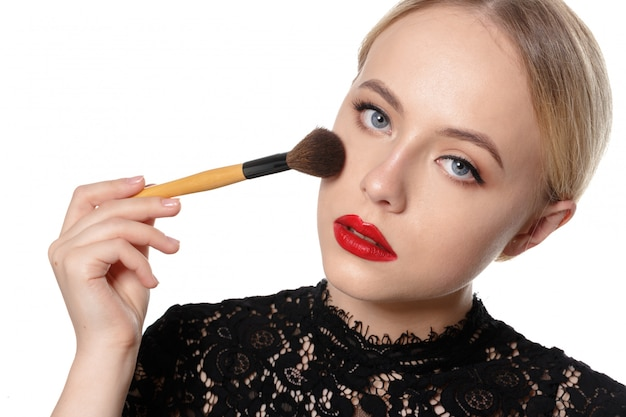 Retrato da beleza de uma bela mulher seminua sorridente posando com pincéis de maquiagem