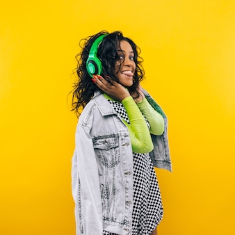 Retrato da beleza de uma jovem afro-americana com um penteado afro. garota posando em fundo amarelo, olhando para a câmera, sorrindo. tiro do estúdio.