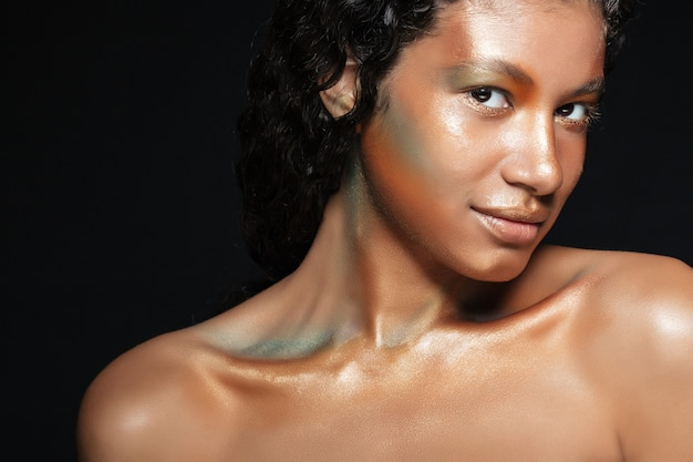 Retrato da beleza de uma jovem americana atraente com maquiagem elegante sobre preto
