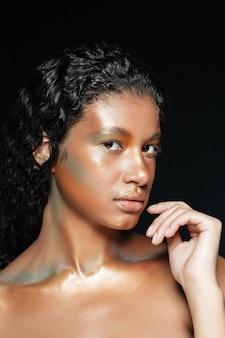 Retrato da beleza de uma jovem americana bonita com maquiagem fashion sobre preto